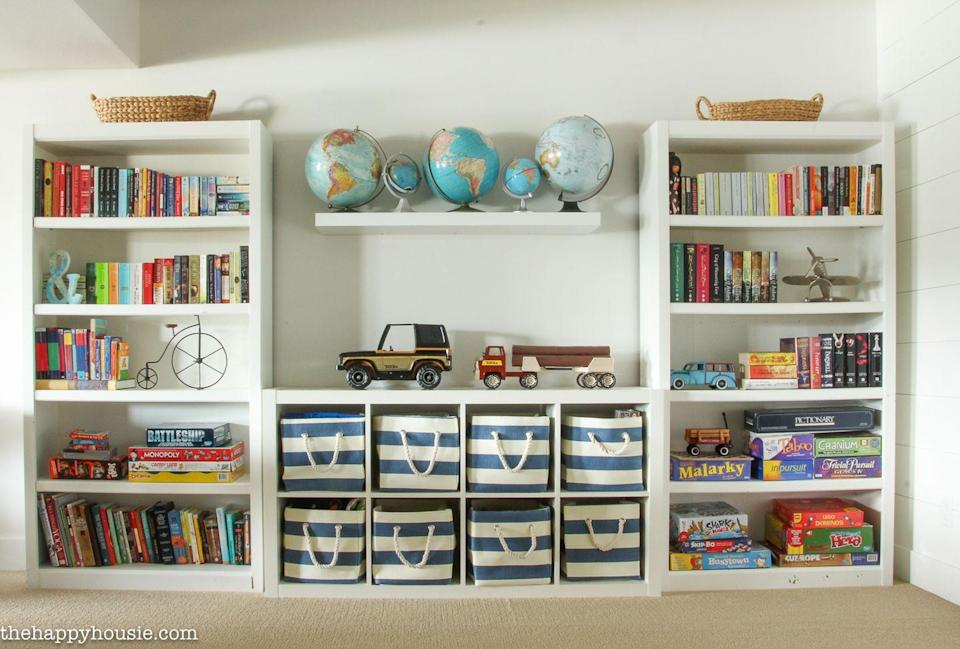 """<p>Turn toys into decor by displaying your child's collection of vintage toy cars or globes on open shelving in the playroom.</p><p><strong>See more at <a href=""""https://thehappyhousie.porch.com/three-simple-steps-to-an-organized-playroom/"""" rel=""""nofollow noopener"""" target=""""_blank"""" data-ylk=""""slk:The Happy Housie"""" class=""""link rapid-noclick-resp"""">The Happy Housie</a>.</strong></p><p><strong><a class=""""link rapid-noclick-resp"""" href=""""https://www.amazon.com/DII-Collapsible-15x10x12-Pinstripe-Nautical/dp/B076HN8Y24/ref=asc_df_B076HN8Y24/?tag=syn-yahoo-20&ascsubtag=%5Bartid%7C10063.g.36014277%5Bsrc%7Cyahoo-us"""" rel=""""nofollow noopener"""" target=""""_blank"""" data-ylk=""""slk:SHOP FABRIC BINS"""">SHOP FABRIC BINS</a><br></strong></p>"""