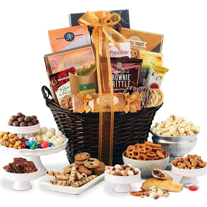 """<p><strong>Broadway Basketeers</strong></p><p>amazon.com</p><p><strong>$49.95</strong></p><p><a href=""""https://www.amazon.com/dp/B00FBGKCHE?tag=syn-yahoo-20&ascsubtag=%5Bartid%7C10055.g.19694294%5Bsrc%7Cyahoo-us"""" rel=""""nofollow noopener"""" target=""""_blank"""" data-ylk=""""slk:Shop Now"""" class=""""link rapid-noclick-resp"""">Shop Now</a></p><p>Flatbread crisps, yogurt cookies, hot cocoa, coffee, and wafer rolls are just few of the delicious items in this gift basket. Amazon reviewers can't get over how great it looked upon arrival. <br></p>"""