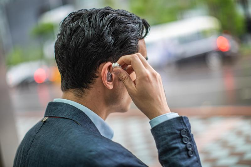 Businessman in the city putting a hearing aid/earphones in the ear