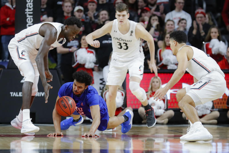 SMU's Isiah Jasey, below, loses control of the ball next to Cincinnati's Mamoudou Diarra, left, during the first half of an NCAA college basketball game Tuesday, Jan. 28, 2020, in Cincinnati. (AP Photo/John Minchillo)