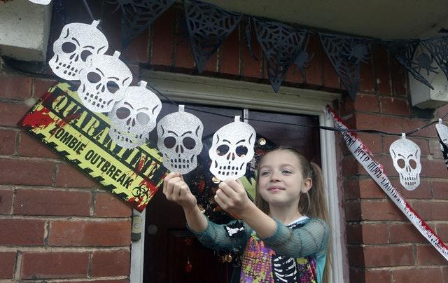 Talulah arranges skull decorations near her front door (Danny Lawson/PA)