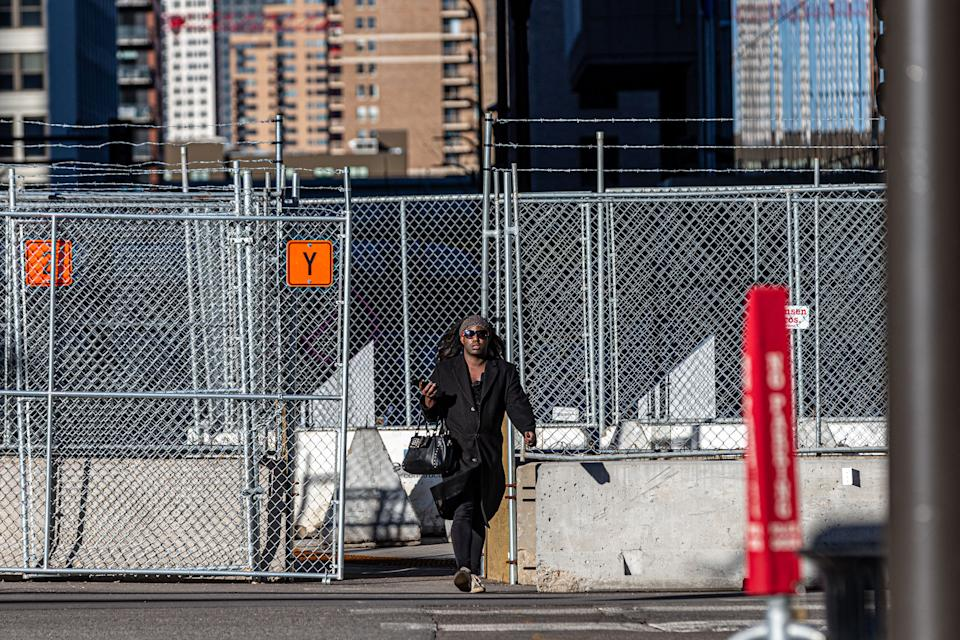 A pedestrian is seen through security barricades set up outside the Hennepin County Government Center on the third day of jury selection in the trial of former Minneapolis Police officer Derek Chauvin on March 11, 2021 in Minneapolis, Minnesota. - A Minnesota judge on March 11, 2021 added an additional murder charge against Derek Chauvin, the police officer on trial for the death of George Floyd. Chauvin, 44, is already facing charges of second-degree murder and manslaughter in connection with Floyd's May 25, 2020 death in Minneapolis. (Photo by Kerem Yucel / AFP) (Photo by KEREM YUCEL/AFP via Getty Images)