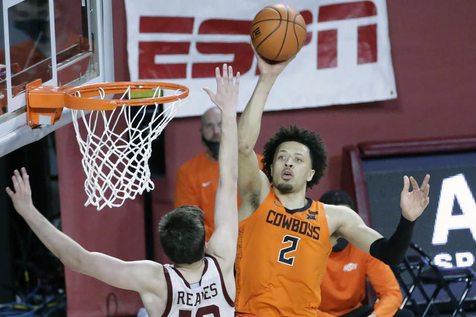 FILE - Oklahoma State guard Cade Cunningham (2) shoots against Oklahoma guard Austin Reaves (12) during overtime of an NCAA college basketball game in Norman, Okla., in this Saturday, Feb. 27, 2021, file photo. Cunnuingham has made The Associated Press All-America first team, announced Tuesday, March 16, 2021.(AP Photo/Garett Fisbeck, File)