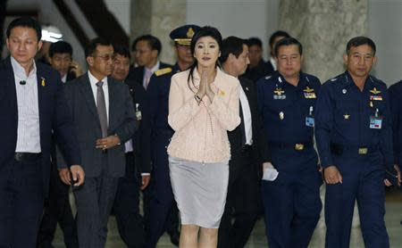 Thai Prime Minister Yingluck Shinawatra gestures while speaking to reporters following following the declaration of a state of emergency in Bangkok