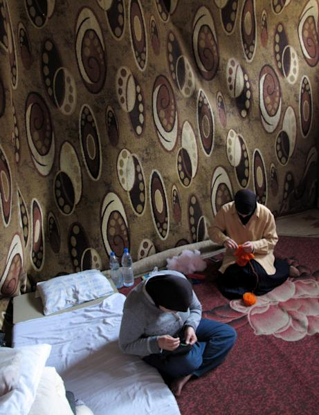 Two Syrian women knit in their room in front of a blanket hung as a partition in an elementary school that has been turned into a shelter in Damascus, Syria, Thursday, Dec. 5, 2013. Around 44 families live in the school, just one set up as Syria deals with more than 5 million displaced people on its soil. (AP Photo/Lee Keath)