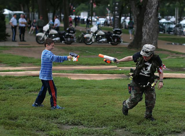WASHINGTON, DC - JULY 03: Lauren Wagner (R) engages in a squirt gun battle during a toy gun rally on the grounds of the Washington Monument July 3, 2013 in Washington, DC. Gun rights advocates participates in the Armed Toy Gun March on D.C. to raise money and toys for the Toys for Tots program. (Photo by Mark Wilson/Getty Images)