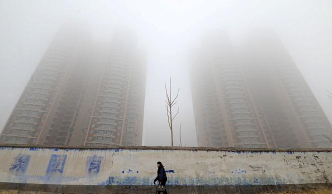 A woman wearing a mask walks past buildings on a polluted day in Handan, Hebei province, China January 12, 2019. Photo: Reuters