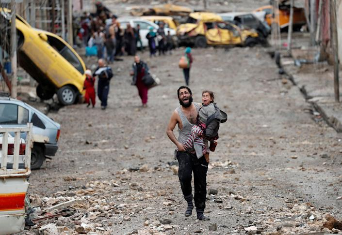 <p>MAR. 4, 2017 – A man cries as he carries his daughter while walking from an Islamic State-controlled part of Mosul towards Iraqi special forces soldiers during a battle in Mosul, Iraq. (Photo: Goran Tomasevic/Reuters) </p>