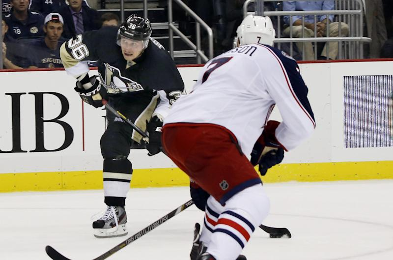Pittsburgh Penguins' Jussi Jokinen, of Finland, left, shoots and scores past Columbus Blue Jackets' Jack Johnson in the second period of the NHL hockey preseason game on Saturday, Sept. 21, 2013, in Pittsburgh. (AP Photo/Keith Srakocic)