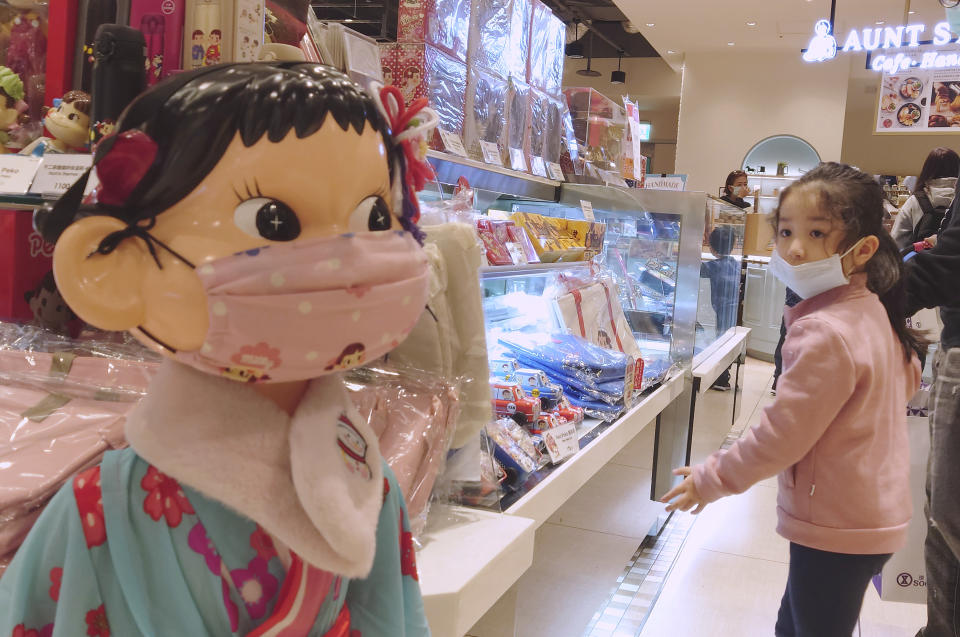 A girl wears a face mask to help curb the spread of the coronavirus and looks at a doll wearing the same at a department store in Taipei, Taiwan, Saturday, Feb. 27, 2021. (AP Photo/Chiang Ying-ying)