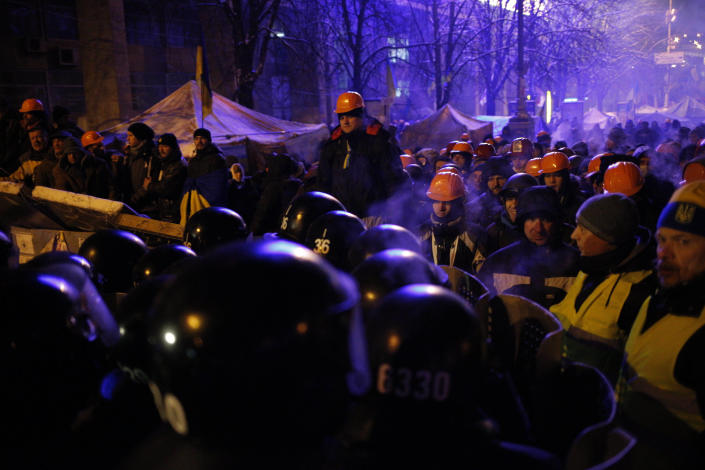 """Riot policemen block Pro-European Union activists camping out in their tents on the Independence Square in Kiev, Ukraine, Wednesday, Dec. 11, 2013. Hundreds of police have moved on a large protest camp in the center of Kiev. Protesters are shouting """"Shame!"""" """"We will stand!"""" and singing the Ukrainian national anthem. (AP Photo/Alexander Zemlianichenko)"""