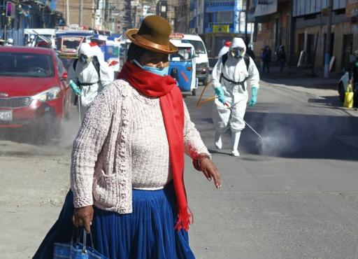 A woman dressed in typical indigenous clothing walks near municipal employees disinfecting the streets of Puno in Peru
