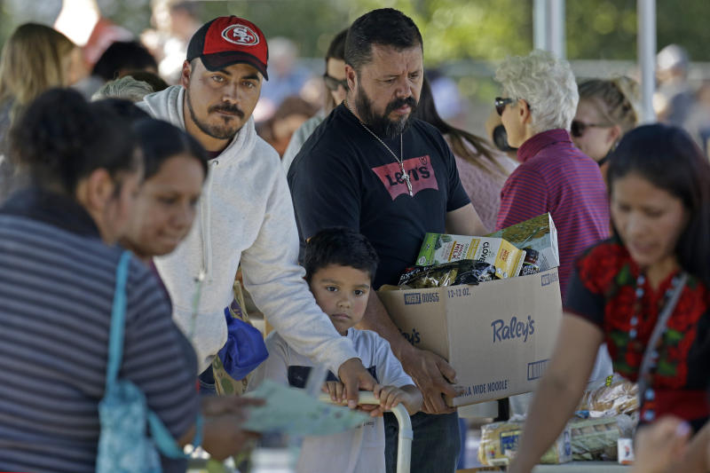 People gather items during a free food distribution for migrant workers evacuated because of the Kincade Fire Thursday, Oct. 31, 2019, in Healdsburg, Calif. (AP Photo/Charlie Riedel)