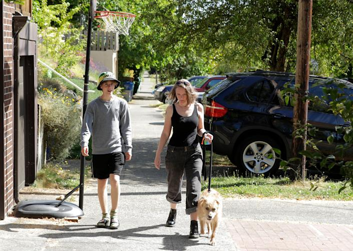 Jennifer Haller, the first person to receive a trial dose of a COVID-19 vaccine, and her son Hayden, 16, walk their dog on Sunday, July 19, 2020.