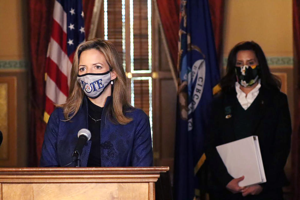 """FILE - In this Wednesday, Oct. 28, 2020 photo provided by the Michigan Office of the Governor, Michigan Secretary of State Jocelyn Benson addresses the state in Lansing, Mich., accompanied by Gov. Gretchen Whitmer, background. """"Just like we have seen a lot of legislators making ill-advised decisions to hold hearings that ended up being more political theater than policy debates, we can similarly expect legislators to further this hyper-partisan agenda to restrict the vote,"""" says Benson, a Democrat. (Michigan Office of the Governor via AP)"""