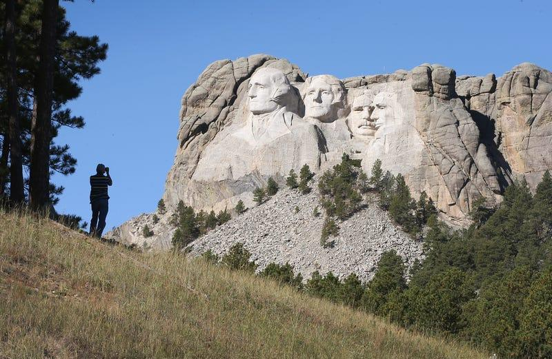 KEYSTONE, SD - OCTOBER 01: A tourist takes a picture of Mount Rushmore National Memorial from outside the park on October 1, 2013 in Keystone, South Dakota.