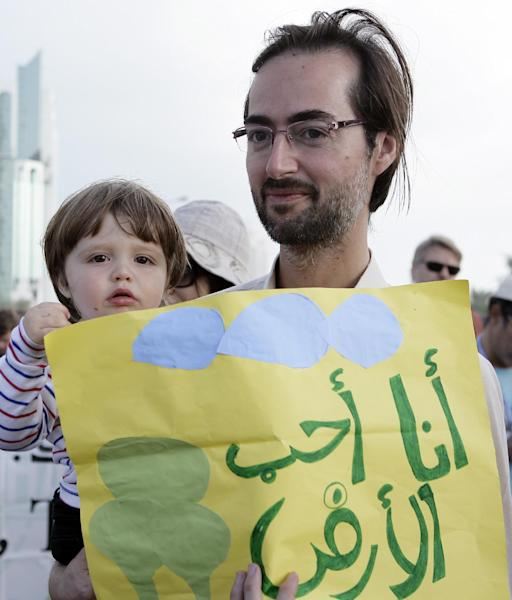 A man with his son holding a banner reading 'I love the earth' as they march with local and international activists to demand urgent action to address climate change at the U.N. climate talks in Doha, Qatar, Saturday , Dec. 1, 2012. (AP Photo/Osama Faisal)