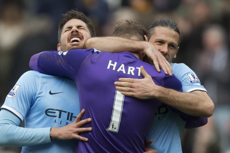 Manchester City's Javier Garcia, left, and Martin Demichelis, right, celebrate with goalkeeper Joe Hart after their 2-0 win against Hull City in their English Premier League soccer match at the KC Stadium, Hull, England, Saturday March 15, 2014. (AP Photo/Jon Super)