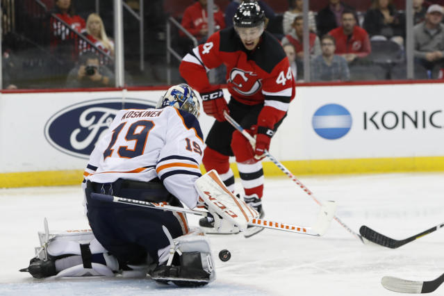 Edmonton Oilers goaltender Mikko Koskinen (19) makes a save as New Jersey Devils left wing Miles Wood (44) watches during the second period of an NHL hockey game Thursday, Oct. 10, 2019, in Newark, N.J. (AP Photo/Kathy Willens)