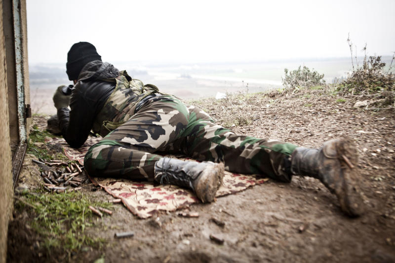 In this Monday, Dec. 17, 2012 photo, a Free Syrian Army fighter scans for Syrian Army positions in Azaz, Syria. (AP Photo/Virginie Nguyen Hoang)