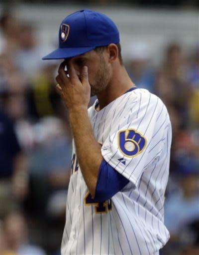 Milwaukee Brewers starting pitcher Johnny Hellweg wipes his face as he walks back to the dugout after the first inning of a baseball game against the New York Mets, Friday, July 5, 2013, in Milwaukee. (AP Photo/Morry Gash)