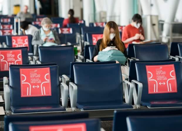Signs remind travellers at Pearson International Airport of pandemic restrictions.