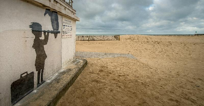 An art piece protected by a plexiglass pane by British artist Banksy, seen on a beach in Calais, northern France