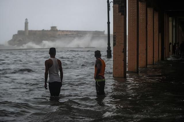 <p>Cubans stand in a flooded street in Havana, on Sept. 10, 2017. (Photo: Yamil Lage/AFP/Getty Images) </p>
