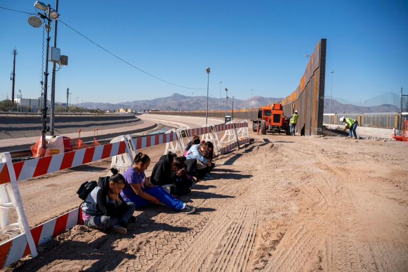Salvadoran migrants wait for a transport to arrive after turning themselves into US Border Patrol by border fence under construction in El Paso, Texas on March 19, 2019. (Photo: PAUL RATJE/AFP/Getty Images)