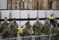 "U.S. National Guard members stand beside crates of medical supplies at the Jacob Javits Center, Monday, March 23, 2020, in New York. New York City hospitals are just 10 days from running out of ""really basic supplies,"" Mayor Bill de Blasio said late Sunday. De Blasio has called upon the federal government to boost the city's quickly dwindling supply of protective equipment. The city also faces a potentially deadly dearth of ventilators to treat those infected by the coronavirus. (AP Photo/John Minchillo)"
