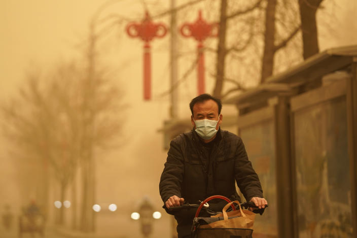 A resident rides through a sandstorm in Beijing, Monday, March 15, 2021. The sandstorm brought a tinted haze to Beijing's skies and sent air quality indices soaring on Monday. (AP Photo/Ng Han Guan)