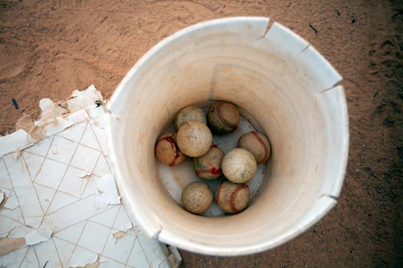 """Baseballs line the bottom of a bucket during practice at the field where Detroit Tigers' Miguel Cabrera learned to play the game, in Maracay, Venezuela, Friday, March 28, 2014. The working class neighborhood of La Pedrera in Maracay, is where the Tigers slugger learned his baseball. Now that he signed the richest contract in baseball history his uncle thinks """"Miguelito"""", as many in his hometown still call him, was destined for greatness, a fact highlighted by the 1.8 million dollar bonus Cabrera received as a 16-year old phenom. (AP Photo/Alejandro Cegarra)"""