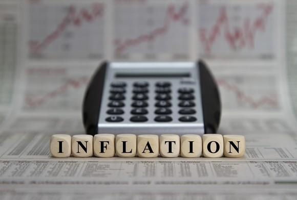 The word inflation spelled out by dice, in front of a calculator and multiple rising charts in a newspaper.
