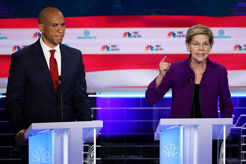 MIAMI, FLORIDA - JUNE 26: Sen. Elizabeth Warren (D-MA) speaks as Sen. Cory Booker (D-NJ) looks on during the first night of the Democratic presidential debate on June 26, 2019 in Miami, Florida. A field of 20 Democratic presidential candidates was split into two groups of 10 for the first debate of the 2020 election, taking place over two nights at Knight Concert Hall of the Adrienne Arsht Center for the Performing Arts of Miami-Dade County, hosted by NBC News, MSNBC, and Telemundo. (Photo by Joe Raedle/Getty Images)