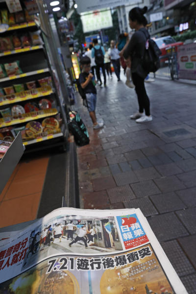 A newspaper front page shows a photo of white shirted thugs attacking commuters at a subway station in Hong Kong at a newsstand on Monday, July 22, 2019. China doesn't want to intervene in Hong Kong's protests but that doesn't mean it won't, as the movement enters its seventh week. (AP Photo/Vincent Yu)