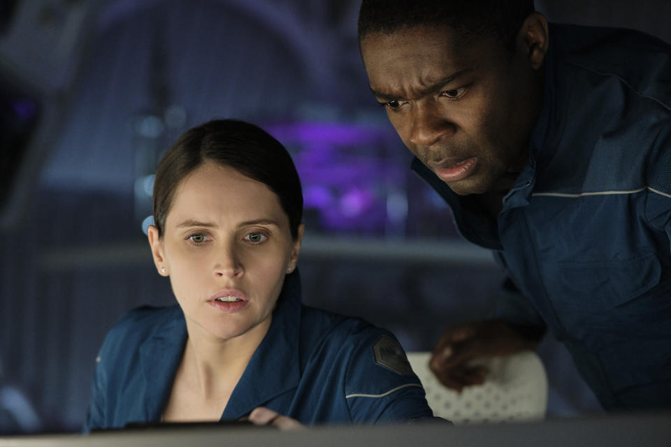 """This image released by Netflix shows Felicity Jones, left, and David Oyelowo in a scene from """"The Midnight Sky."""" (Philippe Antonello/Netflix via AP)"""