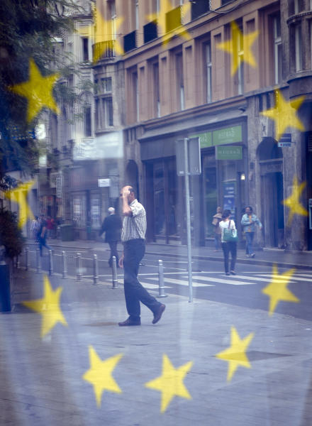A street scene is reflected in the window of a library with an EU flag on display in Zagreb, Croatia, Sunday, June 30, 2013. Croatia is to join the European Union on July 1, 2013. (AP Photo/Darko Bandic)