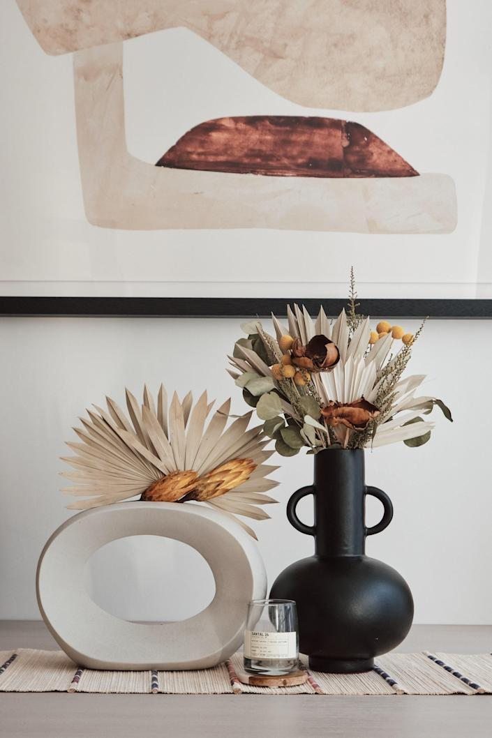 At the center of Candace's table are a pair of black and white vases from Crate & Barrel, containing dried flowers from Raven Rose and Afloral (respectively). Between the vases is the SANTAL 26 candle from Le Labo.