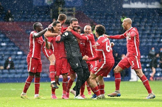 Liverpool goalkeeper Alisson Becker is mobbed by his team-mates