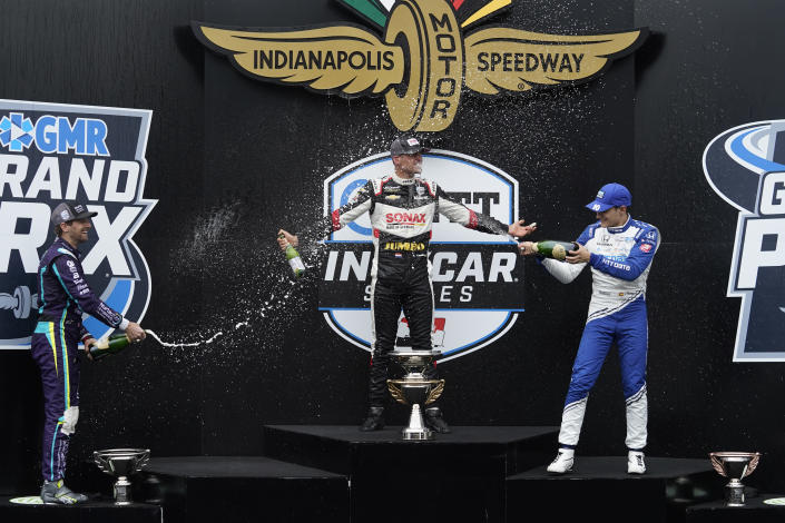 Rinus VeeKay, center, of the Netherlands, celebrates with Romain Grosjean, left, of Switzerland, and Alex Palou, of Spain, after VeeKay won an IndyCar auto race at Indianapolis Motor Speedway, Saturday, May 15, 2021, in Indianapolis. (AP Photo/Darron Cummings)