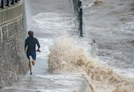Early morning runners in Clevedon, Somerset, were forced to dodge and jump the waves crashing into the seafront on Sunday as Storm Alex continued to batter Britain. (SWNS)
