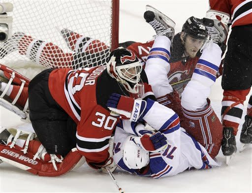 New Jersey Devils goalie Martin Brodeur (30) collides with New York Rangers' Mike Rupp center during the first period of Game 4 of an NHL hockey Stanley Cup Eastern Conference final playoff series, Monday, May 21, 2012, in Newark, N.J. Devils' Anton Volchenkov, of Russia, is at rear. (AP Photo/Kathy Willens)