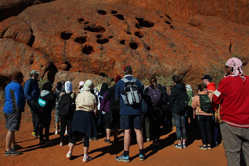ULURU, AUSTRALIA - AUGUST 12: Visitors commence the Mala Walk trail at Uluru on August 12, 2019 in the Uluru-Kata Tjuta National Park, Australia. The Uluru-Kata Tjuta National Park board decided unanimously that the climb will close permanently on October 26, 2019. The date coinciding with the hand-back to traditional owners in 1985 and seen by many as a form of reconciliation. The climb deadline date has sparked a considerable boost in tourism, also aided by cooler weather and the introduction of direct flights to Ayers Rock Airport from cities Darwin and Adelaide. According to Parks Australia Uluru has welcomed 244,075 visitors this calendar year, an increase of 18.7%. Sacred to the Yankunytjatjara and Pitjantjatjara people, climbing Uluru (also known as Ayers Rock) is strongly discou3raged by them for its cultural significance and their concerns for peoples safety. Over 30 people have died and numerous injured while attempting the steep ascent, less than 20% of park visitors take part in the climb. Known as Anangu land, the arkose sandstone formation, 348 meters high is believed to be half a billion years old. The Uluru-Kata Tjuta National Park, jointly managed by Anangu traditional owners and Parks Australia includes Kata Tjuta (The Olgas) and is recognised by UNESCO as a World Heritage Area. (Photo by Lisa Maree Williams/Getty Images)