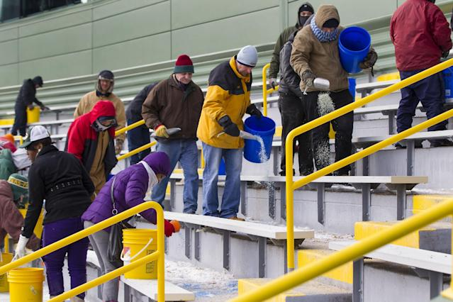 Workers clear ice and snow from the seats at Lambeau Field on Friday, Jan. 3, 2014, in Green Bay, Wis. in preparation for Sunday's NFL football wild-card playoff game between the Green Bay Packers and San Francisco 49ers. (AP Photo/Mike Roemer)
