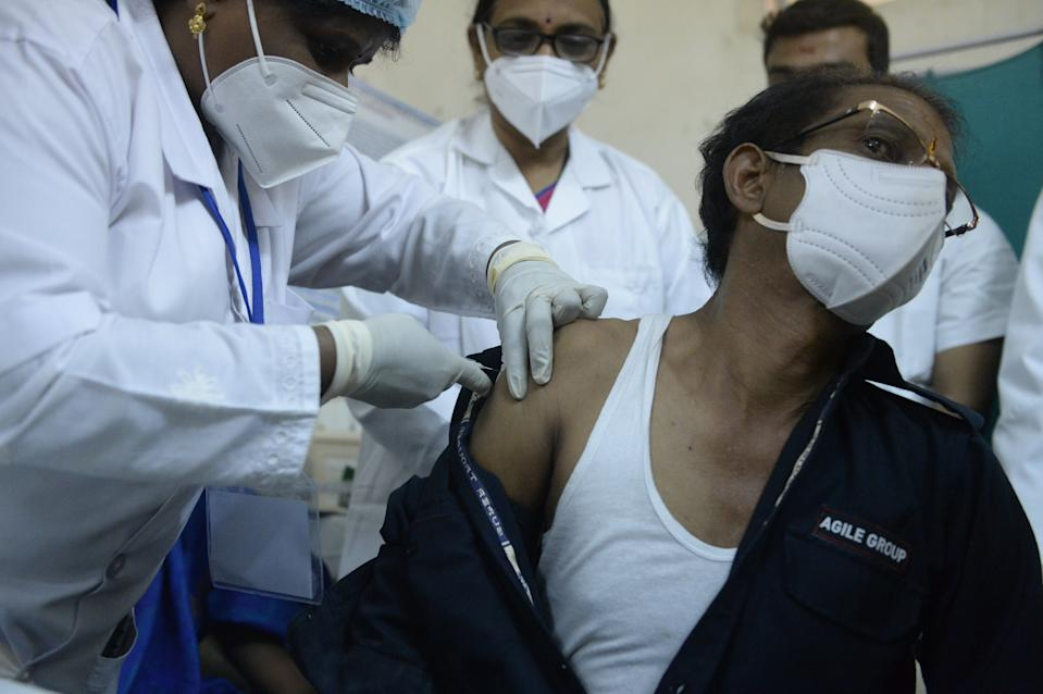A medical worker inoculates a security guard with a Covid-19 coronavirus vaccine at the King Koti hospital in Hyderabad on January 16, 2021. (Photo by Noah SEELAM / AFP) (Photo by NOAH SEELAM/AFP via Getty Images)