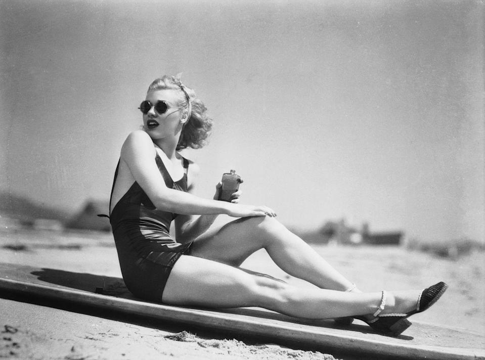 <p>American dancer and actress Ginger Rogers rubs sun lotion onto her legs before sunbathing on the beach, circa 1936.</p>