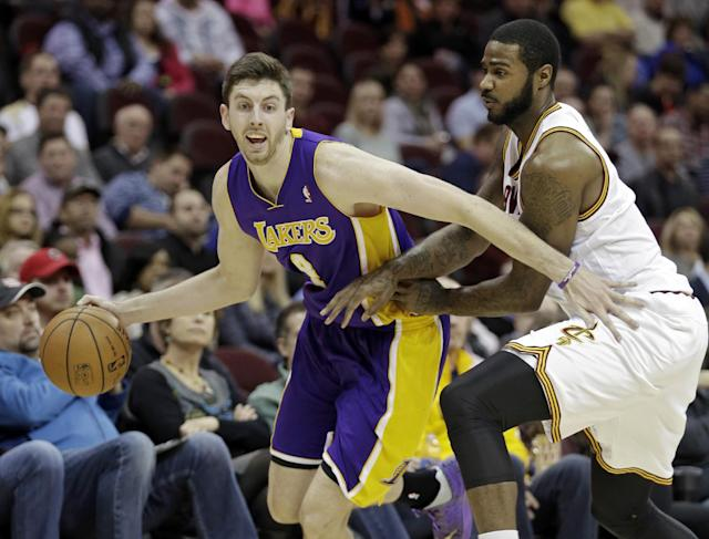Los Angeles Lakers' Ryan Kelly, left, tries to drive around Cleveland Cavaliers' Earl Clark in the second quarter of an NBA basketball game on Wednesday, Feb. 5, 2014, in Cleveland. (AP Photo/Mark Duncan)