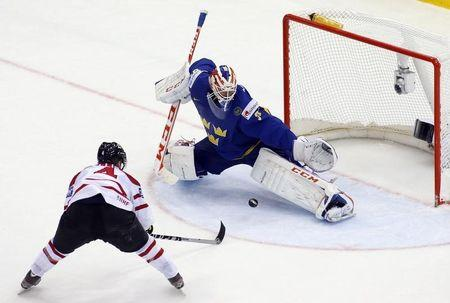 Canada's Ellis scores past Sweden's goalie Nilsson during the extra time period of their men's ice hockey World Championship Group A game at Chizhovka Arena in Minsk