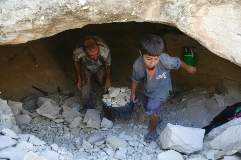Abu Ahmad and his young son have chipped away at stone walls with metal rods and hammers to enlarge the cave their family is using for shelter (AFP Photo/Zein Al RIFAI)