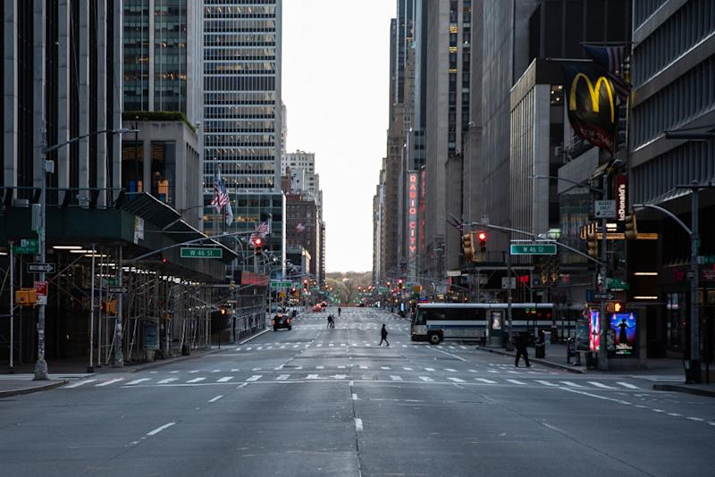 Pedestrians walk along a nearly empty street in Manhattan. Source: Getty